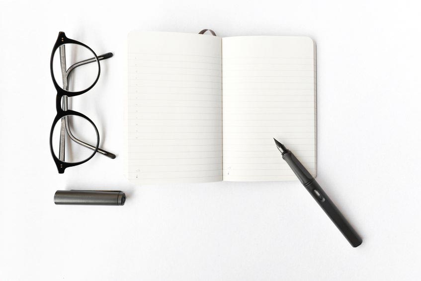 Blank diary, pen, and glasses