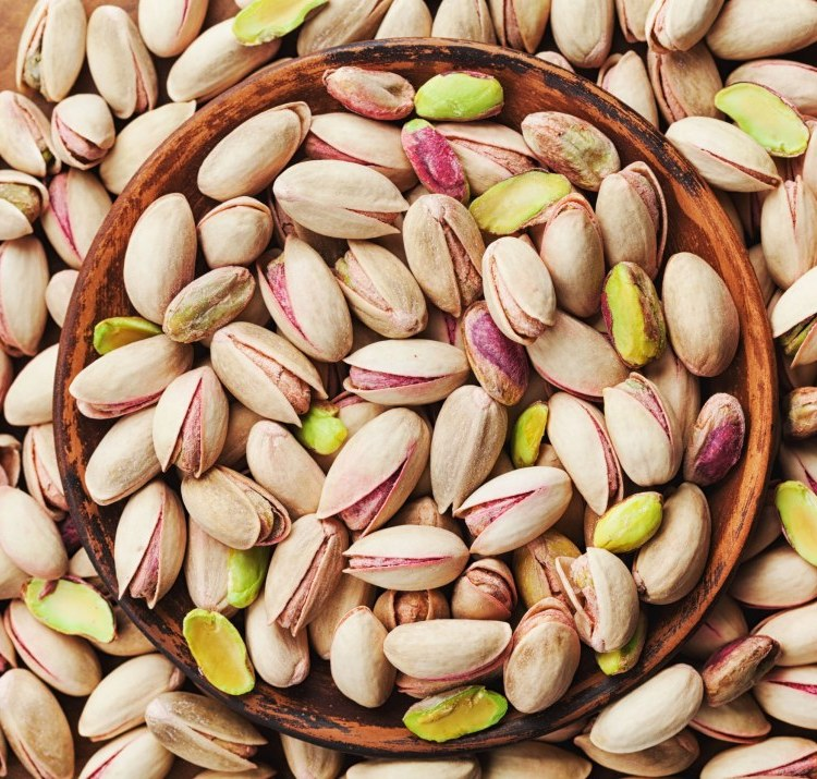 Bowl of pistachio nuts on wooden table top view.