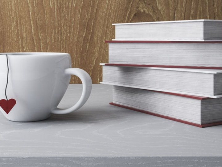 Stack of white books and coffee cup.